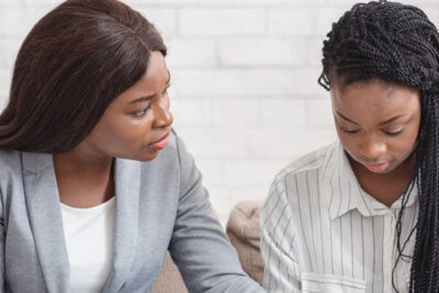 psychologist comforting depressed female patient during therapy session