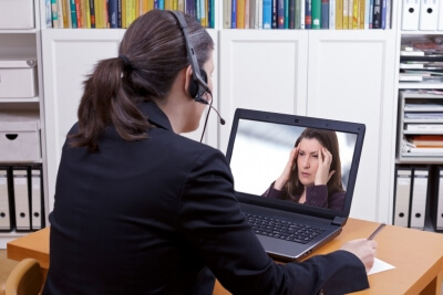 woman with headset in front of her laptop writing something on a paper while making a live video call with a patient